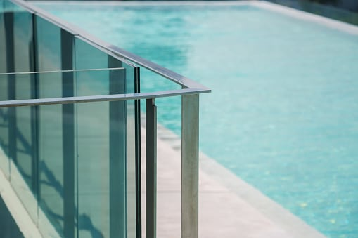 closeup modern flat stainless railing and glass wall on outdoor poolside.